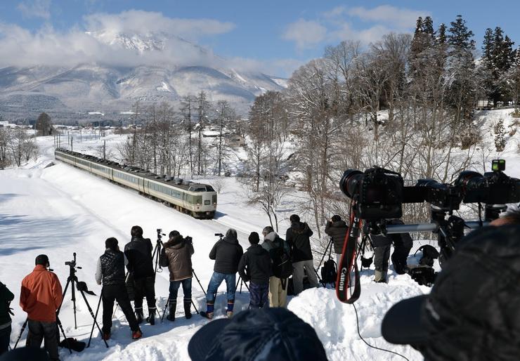 雪原と黒姫山を背景にJR信越線を走る「189系」を写真に収めようと集まった鉄道ファン