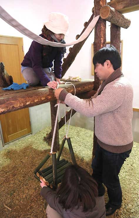 竹の筒を組み合わせたブランコを取り付ける参加者ら