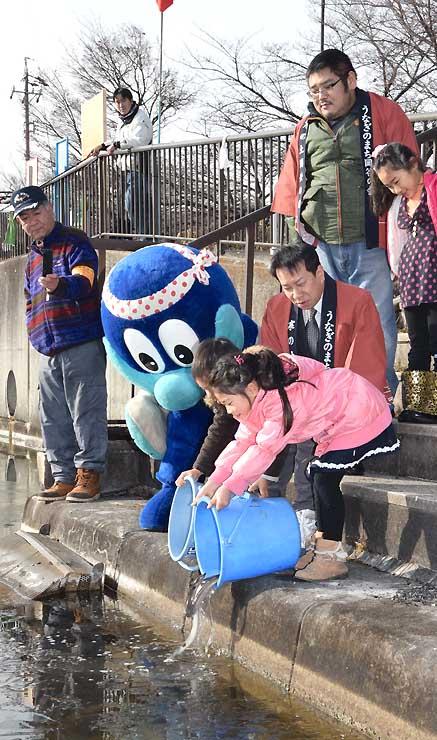 寒の土用丑の日の供養祭で、諏訪湖にウナギを放流する小学生