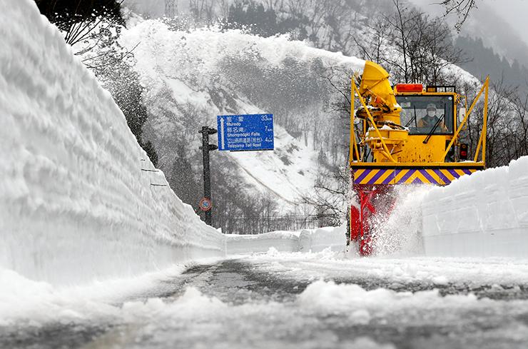 雪を吹き上げながら進むロータリー車=立山町芦峅寺