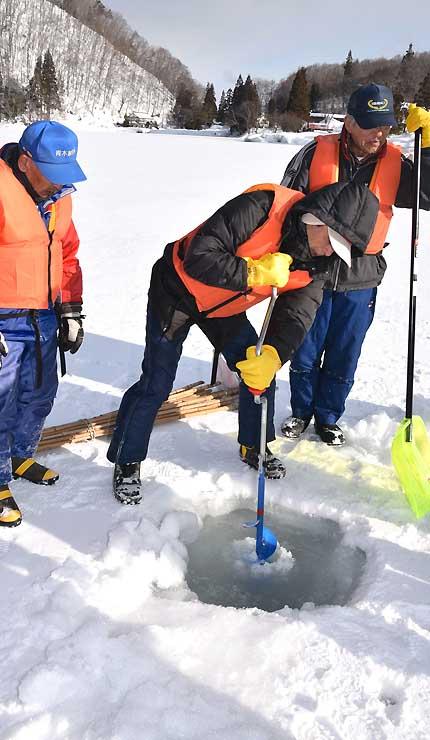 氷に穴を開けて厚さを調べる組合員たち=28日、中綱湖