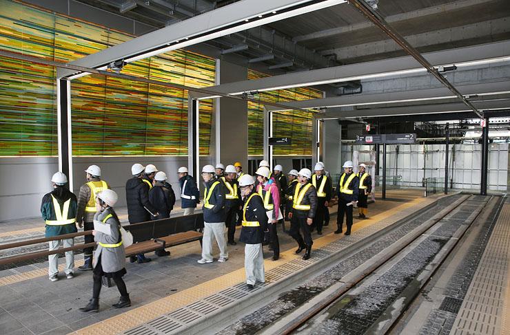 市内電車の新停留場「富山駅」で「トランジット・ライティング・ウォール」(左奥)を視察する富山市議ら=北陸新幹線富山駅高架下