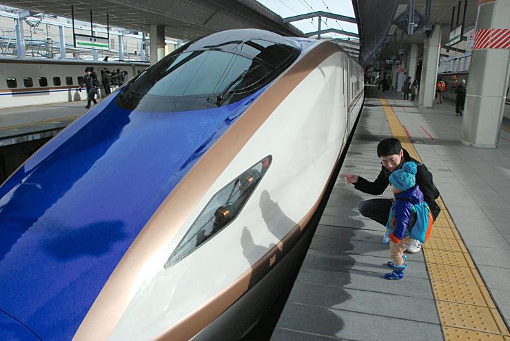 新しい発車メロディーを聞く親子連れ。父親は「新鮮で良い」=31日、JR長野駅