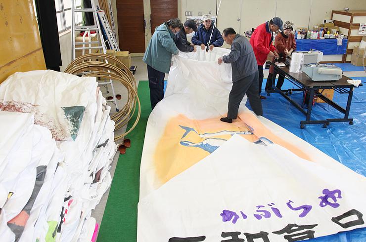 巨大紙風船の仕上げ作業に励む住民たち