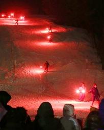 幻想的な赤い光がゲレンデに広がった「たいまつ滑降」=31日、上越市の金谷山スキー場