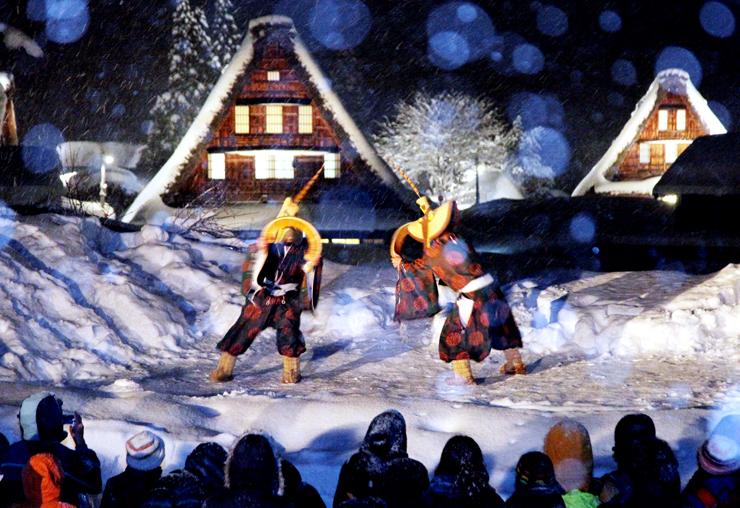 雪の夜空に浮かぶ合掌造りを背景に披露された「こきりこ」のささら踊り=南砺市菅沼