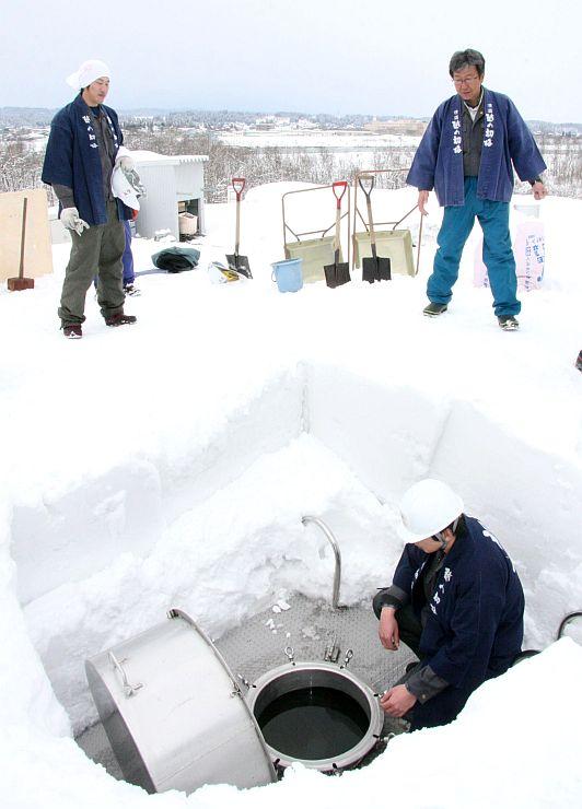 敷地内の雪を集め、雪中貯蔵酒のタンクを埋める高の井酒造の社員=29日、小千谷市東栄3
