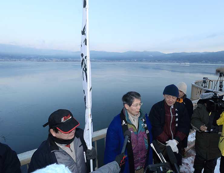 薄氷の諏訪湖を背に、今冬は御神渡りができない可能性が高いと話す八剣神社の宮坂宮司(左から2人目)=4日午前6時55分、諏訪市豊田