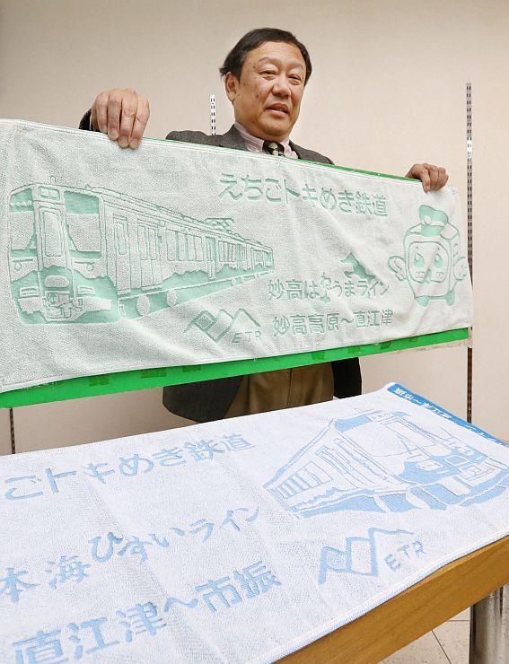 えちごトキめき鉄道の公認グッズ第1号となったタオルと企画した黒川弘司さん=3日、上越市本町4