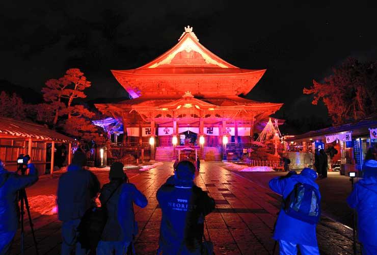 試験点灯でライトアップされた善光寺本堂=6日午後6時22分、長野市