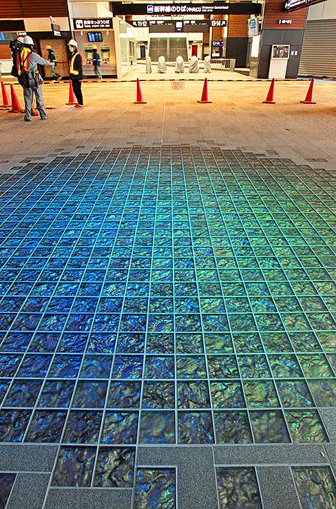 天井の照明の光で青っぽく輝く「フロア・シャンデリア」。奥は北陸新幹線の改札口=10日、北陸新幹線富山駅の南北自由通路