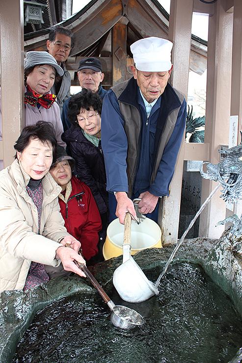 湧き水をくむ久保さん(右)とメンバーら