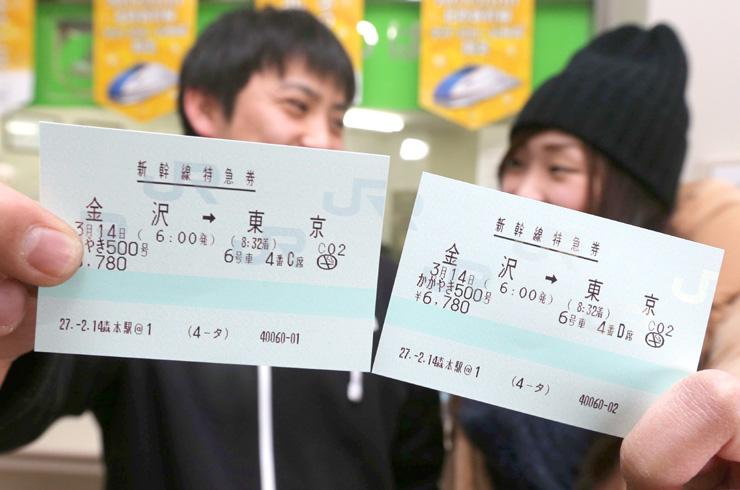 金沢発の「かがやき」始発の切符を手にするカップル=14日午後0時5分、JR森本駅