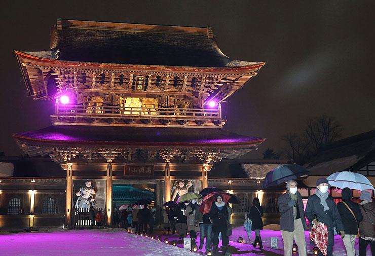 厳かに照らされた山門前を歩く大勢の人たち=高岡市関本町の瑞龍寺