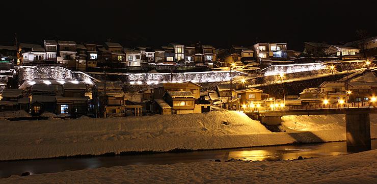 ライトアップされた井田川沿いの禅寺坂やその上に立つ家々=富山市八尾町西町