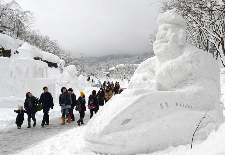 住民らが作った新幹線や高校の校舎などの雪像が並び、大勢の人でにぎわう「第33回いいやま雪まつり」=14日、飯山市城北グラウンド