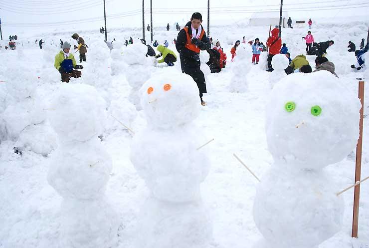 雪玉を三つ重ねた「スノーマン」を作る参加者。630人が参加し、1時間に1585体を作った