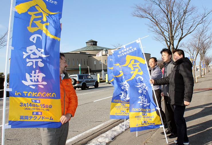 高岡テクノドーム(奥)の近くにのぼり旗を設置するメンバー=高岡市二塚
