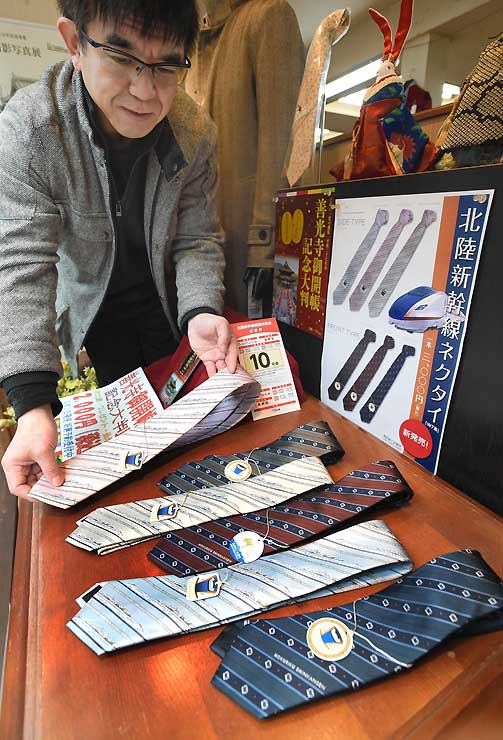 県内でも販売が始まったW7系をあしらったネクタイ=19日、長野市権堂アーケードの洋品店