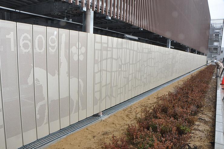 高岡の歴史をデザインした全長約100メートルのアルミアート。1609年の前田利長公の高岡入城=高岡市下黒田の新高岡駅立体駐車場