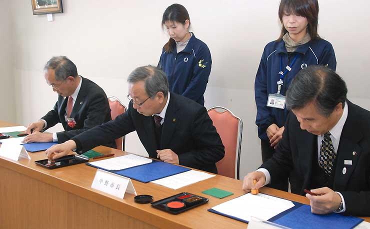 3市の連携を定めた文書に調印する3市長=20日午前、飯山市役所