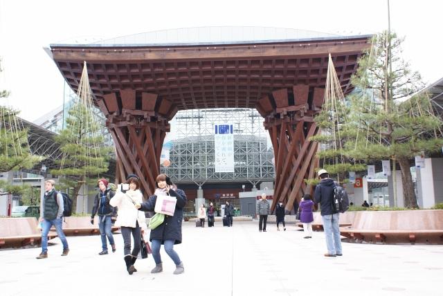 JR金沢駅の鼓門で記念撮影する観光客=2月2日、金沢市木ノ新保町