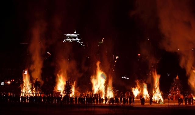 勝山城博物館を背に勢いよく火柱が上がった勝山左義長まつりのどんど焼き=22日夜、勝山市の九頭竜川弁天緑地(多重処理)
