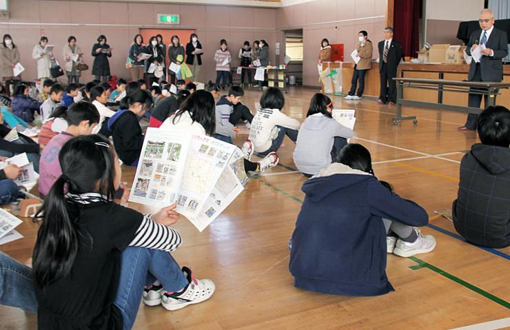 栗田城址のパンフレットについて説明を聞く児童たち