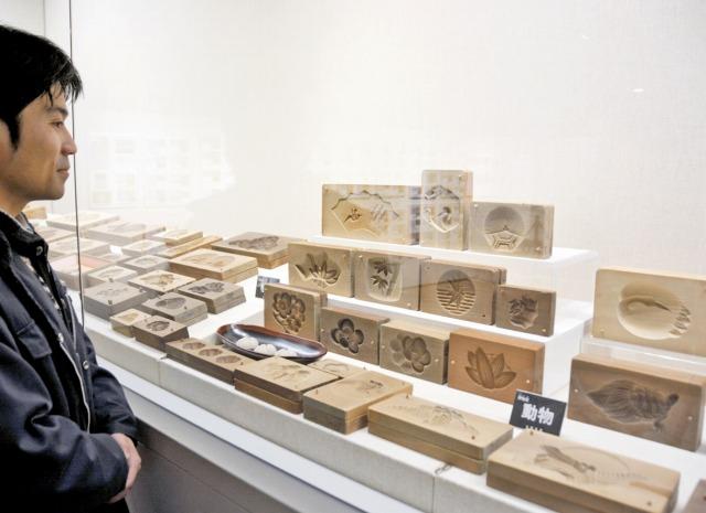 かつて結婚式などで出された和菓子の木製型などが多数並ぶ企画展=24日、福井県若狭町の若狭三方縄文博物館