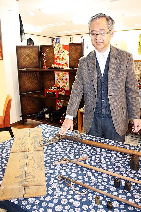 かつて店先に掲げられていた看板や、店で使われていた天秤棒を前に、「アート展で地域を盛り上げたい」と話す井山理事長