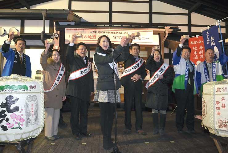地酒での乾杯運動の記念セレモニーで、家高里永子さん(中央)の発声で乾杯する参加者=25日夜、木曽町福島の千村茶屋
