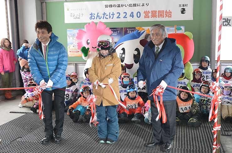 スキー場の営業開始を祝ってテープカットをする、右から瀬戸村長、作野さん、一ノ本社長=26日午前9時2分、王滝村の「おんたけ2240」