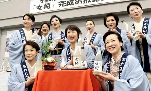 オリジナル日本酒「女将」を手に笑顔のおかみたち=26日、あわら市舟津の芦原温泉旅館会館