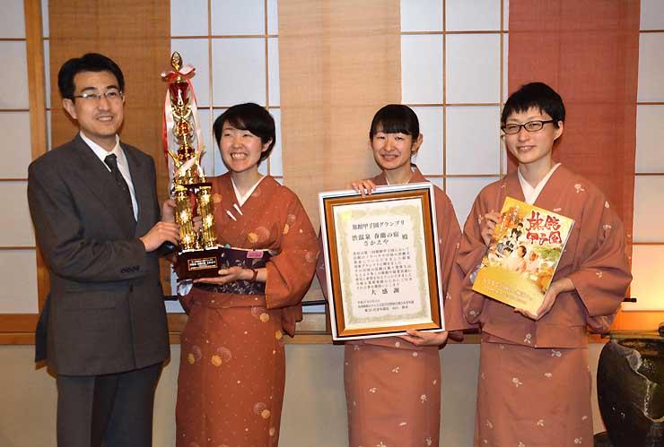 「旅館甲子園グランプリ」のトロフィーや賞状を手にする湯本社長(左)や旅館従業員ら
