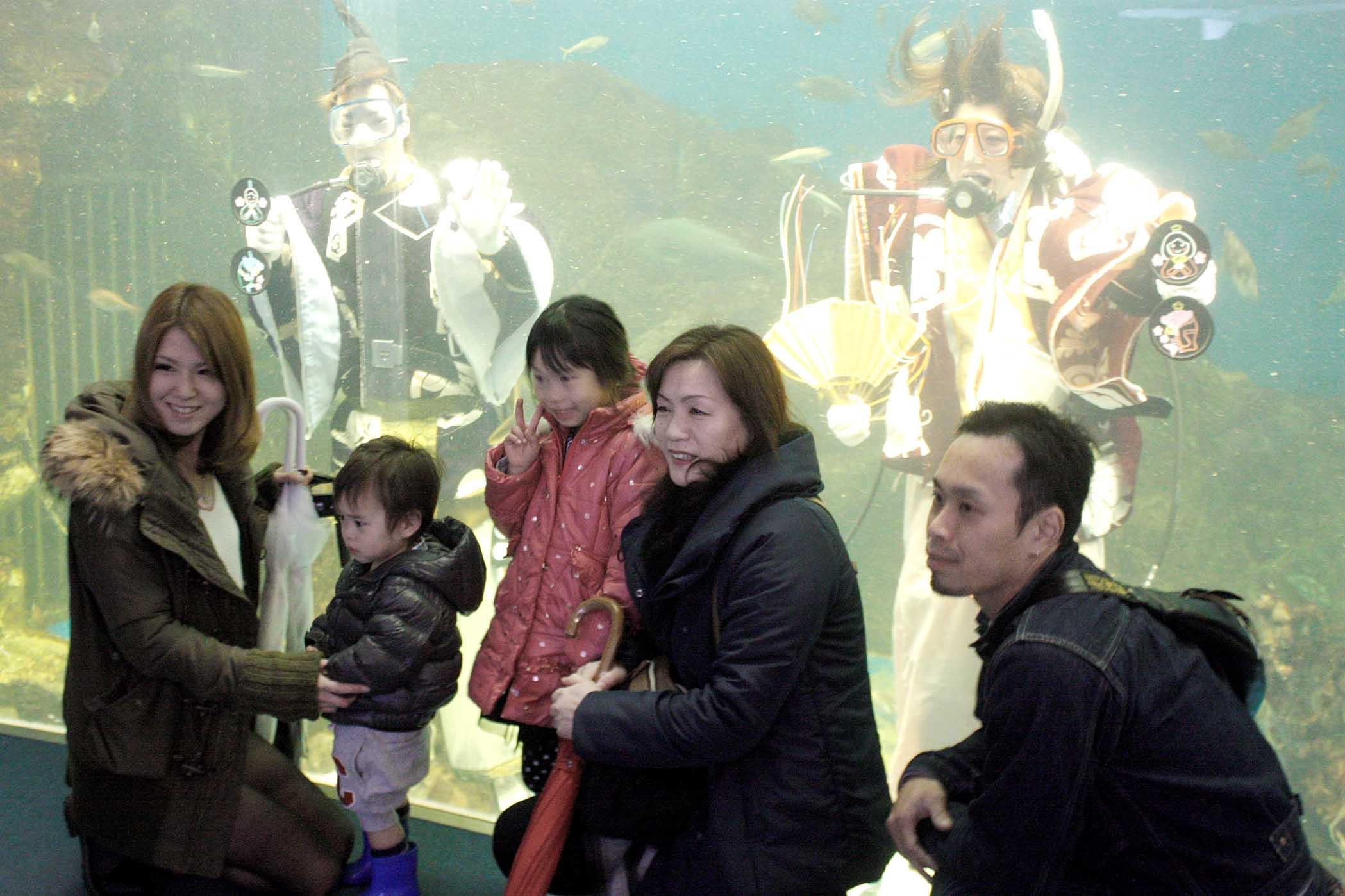 ひな人形の衣装を着た飼育員と記念撮影する来館者=七尾市ののとじま臨海公園水族館