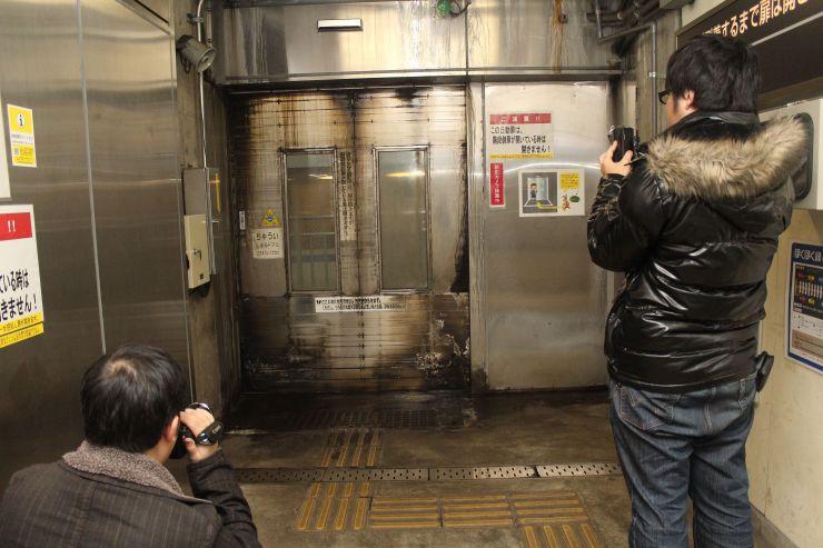 扉の向こうを駆け抜ける「はくたか」の写真や映像を収める鉄道ファンら=十日町市の美佐島駅