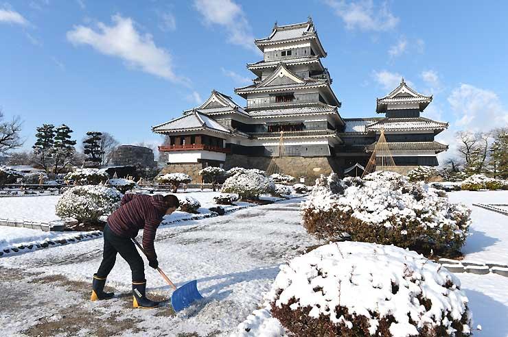 松本城管理事務所職員が雪かきに追われた松本城本丸庭園=2日午前8時16分