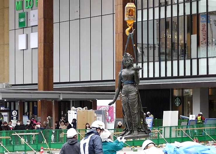 大勢の人に見守られ、長野駅前に再び設置された如是姫像=3日午後2時38分、長野市