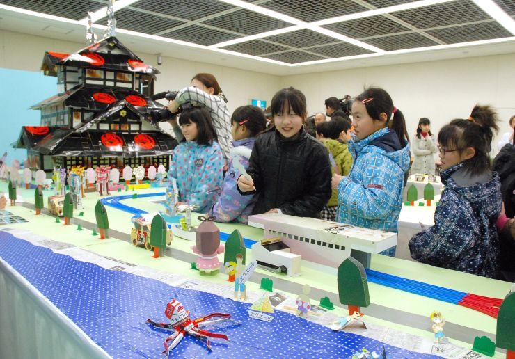 糸魚川駅や三重櫓などに見入る子どもたち=3日、上越市
