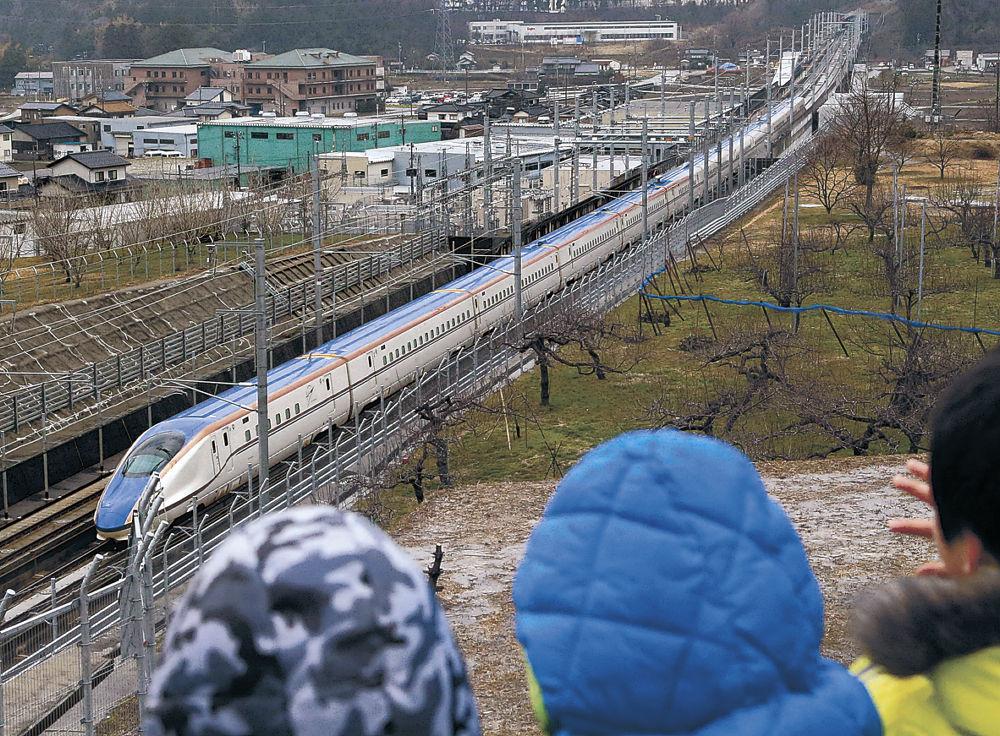 フェンスの間から、新幹線車両に笑顔で手を振る園児