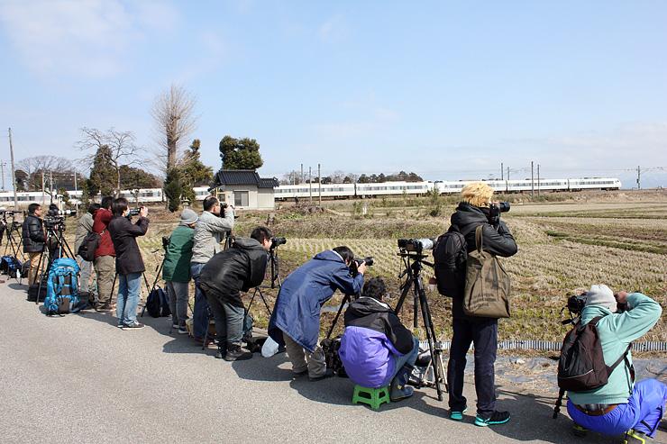 特急「はくたか」をカメラに収める鉄道ファン=富山市野田