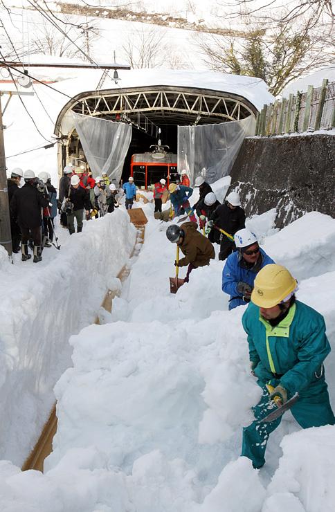 1メートル50センチ前後の雪に埋もれた立山ケーブルカーの軌道を、スコップで掘り出す作業員=立山町千寿ケ原の立山駅周辺