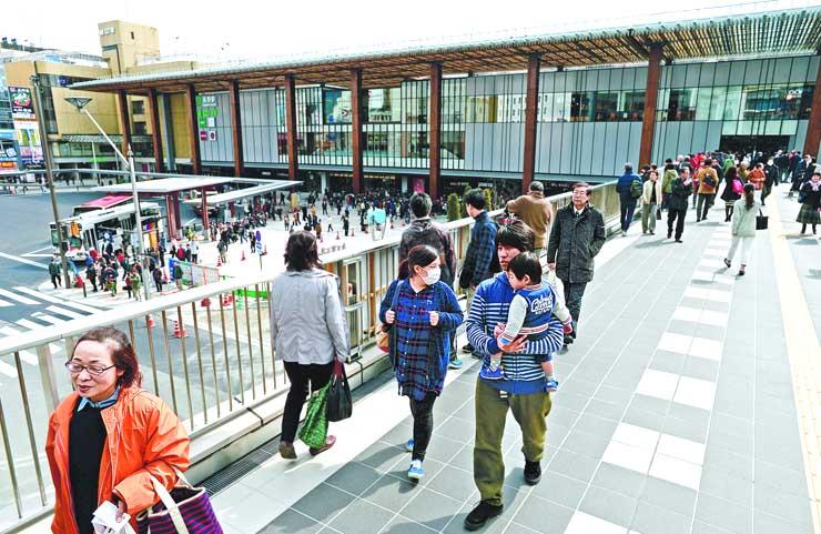 長野駅の新駅ビルとウエストプラザ長野をつなぐ歩行者専用デッキを歩く人たち=7日午前11時15分、長野市