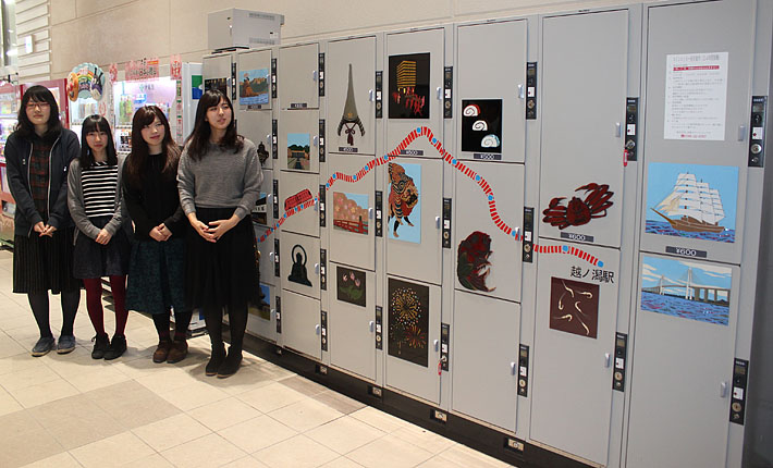 漆の装飾が施されたコインロッカーを眺める富山大芸術文化学部の学生