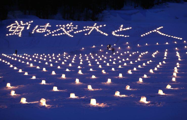 仁上会場の雪原を埋めるキャンドル。夏のホタルで有名な仁上集落は光景を「雪ほたる」と表現していた=2月28日、上越市大島区