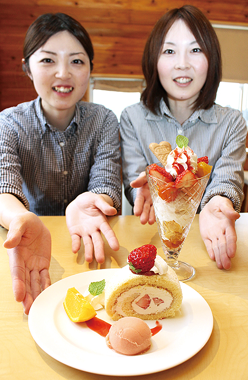 自家栽培トマトと射水産イチゴを使い、瑞穂さん(右)と薫さんが考案したパフェ(右奥)とロールケーキ