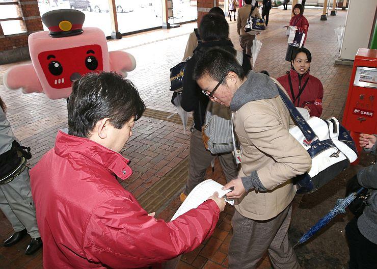 時刻表を利用者に配るえちごトキめき鉄道の社員=12日、上越市のJR高田駅