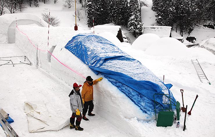 開業日に向け、急ピッチで進められている北陸新幹線の雪像造り=南砺市相倉合掌造り集落