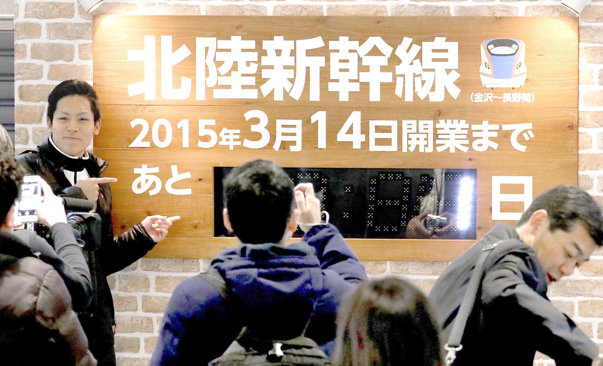 開業まで「あと1日」と表示されたカウントダウンボードと記念撮影する駅利用者=13日午前9時半、JR金沢駅
