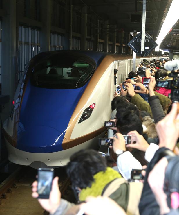 大勢の人に見送られ、東京に向かって出発する北陸新幹線の一番列車「かがやき500号」=14日午前6時1分、JR金沢駅